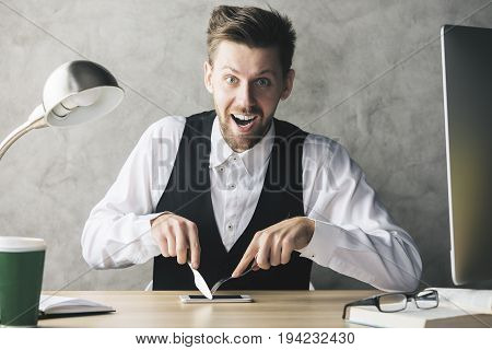 Crazy businessman about to eat phone with a knife and fork while sitting at wooden office desk with coffee cup and other items
