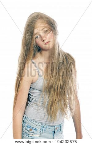 young and sad teen girl hides behind blond wavy hair against white studio background