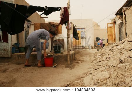 Khiva Uzbekistan - March 08 2009: Woman hanging laundry after washing