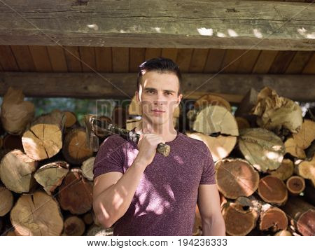 A handsome young man with an ax on his shoulder and lots of wood in the background