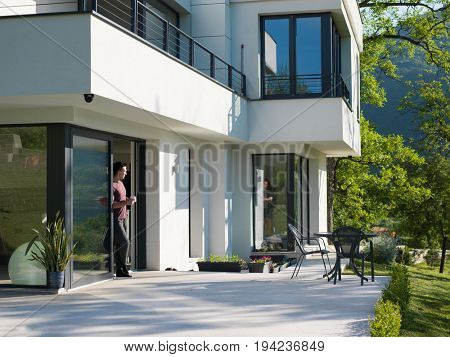 portrait of a young successful man drinking coffee in the doorway of his luxury home villa