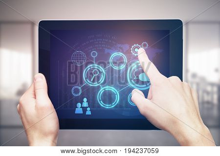 Male hands using tablet with blue business hologram on blurry office interior background. Presentation concept. 3D Rendering