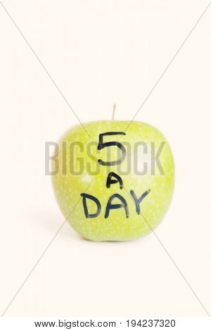 Close-up of sayings text on a granny smith apple over white background