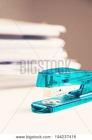 Stapler on white table with stack of papers in background