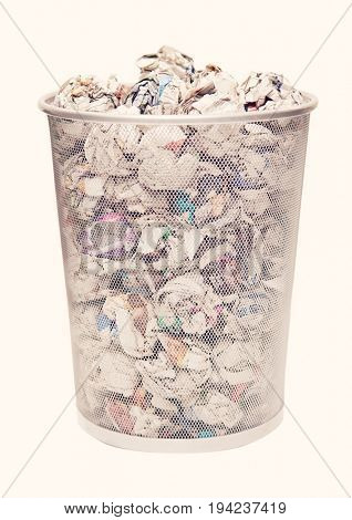 Wastebasket full of crumpled paper over white background
