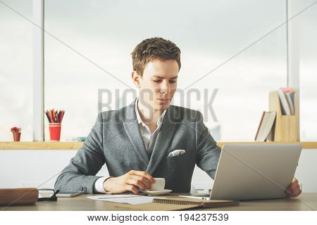 Attractive caucasian male worker drinking coffee and using laptop in modern office with blurry city view and items on desktop
