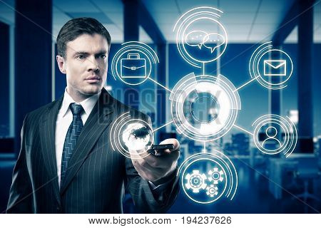Businessman holding smartphone with abstract digital business hologram in dark office room with night city view. Technology concept. 3D Rendering