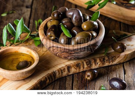 Olives and olive oil in olive wooden bowls on olive wooden cutting board, olive tree branch on wooden rustic background