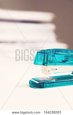 Blue stapler on table with stack of papers in background