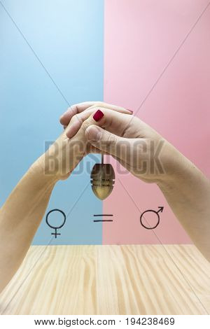 The hands of a man and a woman holding a dumbbell next to the symbol of gender equality