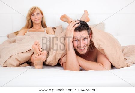 Unhappy couple sitting angry in bed