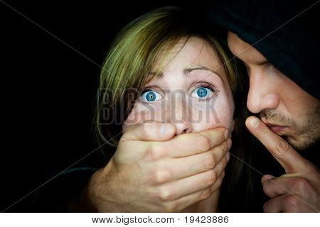 Man terrifying female holding mouth to make her silent