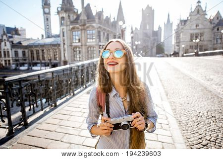 Portrait of a young woman tourist with photo camera traveling in the old town of Gent city during the sunrise in Belgium