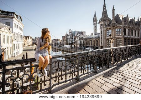 Young woman tourist sitting on the bridge in the old town of Gent city durnig the sunrise in Belgium