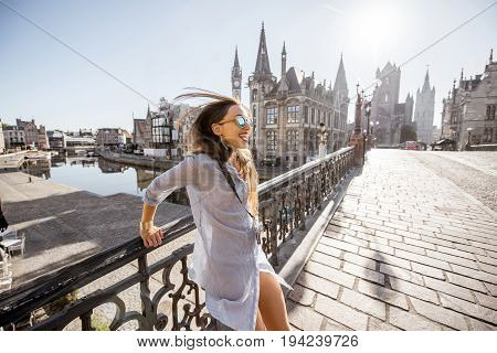 Young woman tourist having fun jumping on the bridge in Gent city in Belgium