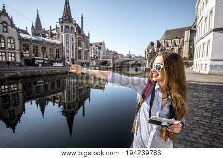 Young woman tourist walking with photo camera near the water channel with great view on the old town in Gent city in Belgium