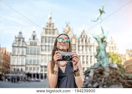 Portrait of a young woman tourist with photo camera on the Great Market square in Antwerpen city in Belgium