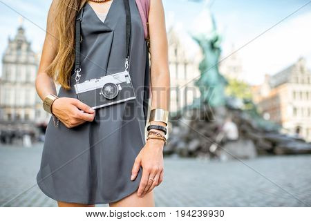 Woman tourist with photo camera standing on Great Market square background in Antwerpen city, Belgium