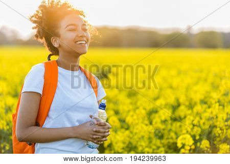 Outdoor portrait of beautiful happy laughing mixed race African American girl teenager female young woman with drinking water bottle in a field of yellow flowers at sunset in golden evening sunshine