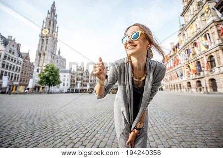 Young and happy woman tourist showing ok standing on the Great Market square during the morning in Antwerpen, Belgium