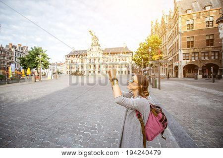Young woman tourist photographing wiht phone on the Great Market square in Antwerpen, Belgium
