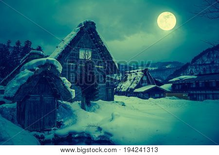 Snow Covered The Ground In Winter. Town With Night Sky And Full Moon. Cross Process.
