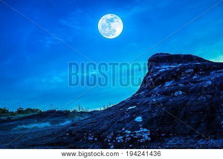 Landscape Of The Rock Against Blue Sky And Full Moon Above Wilderness Area In Forest.