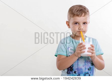 Portrait of a nice little boy in a blue T-shirt,  with a glass of milk and yellow straw. A cute little kid drinking a milk from a yellow straw on gray background.