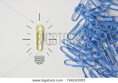 Individuality symbol and independent thinker concept and new leadership concept or individuality as a group of paperclip on canvas with one individual in the opposite direction as a business icon.