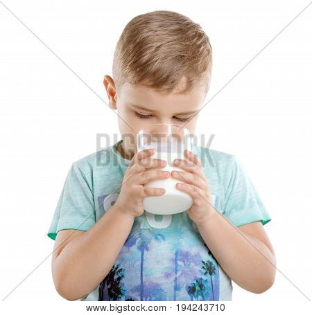Concept of healthy food and drinks. Pretty little boy is drinking milk from a glass. Close-up portrait of cute little child is drinking milk, isolated on a white background.