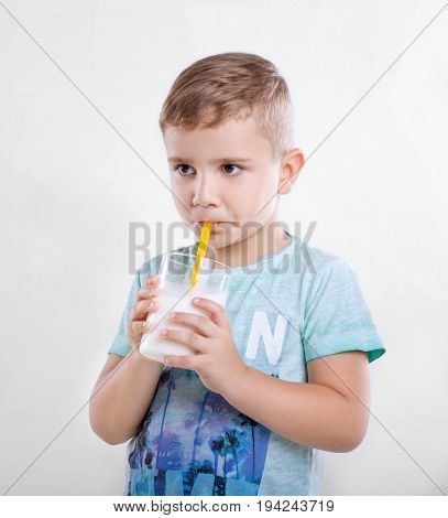 Pretty little boy is drinking milk in a glass from a yellow straw. Close-up portrait of cute little kid is drinking milk from yellow straw in the morning on gray background. Concept of healthy living, food  drink, family.