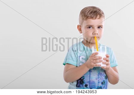 A cute little child with a glass full of fresh milk. Pretty little boy is drinking a glass full of milk from yellow straw on a gray blackground. Beautiful little boy is holding glass with milk shake.