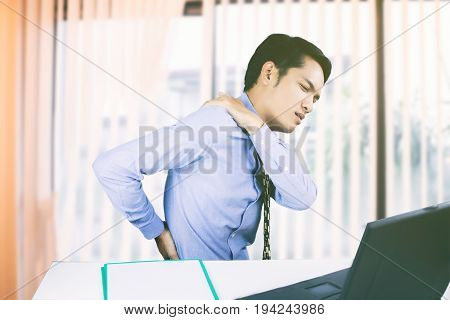 Asian Business men with back pain sin an office and serious about the work done until the headache on working hard