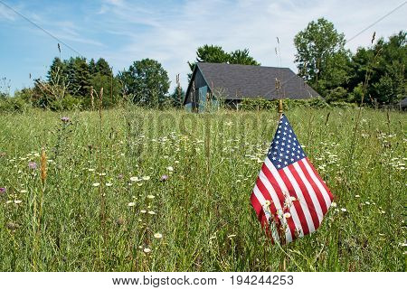 American flag and wildflowers in rural meadow with old barn in background
