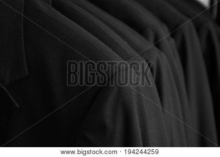 row of black tuxedo jackets hanging in closet