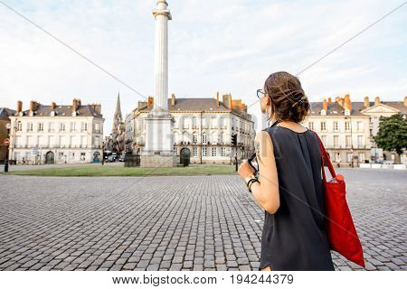 Young woman tourist enjoying beautiful view on the Marechal-Foch square with Loise column in Nantes city in France
