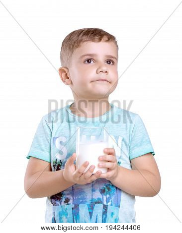 Close-up portrait of a nice little boy with a glass of organic milk isolated on a white background. Beautiful little boy with a glass of milk wondering about it's amazing taste.