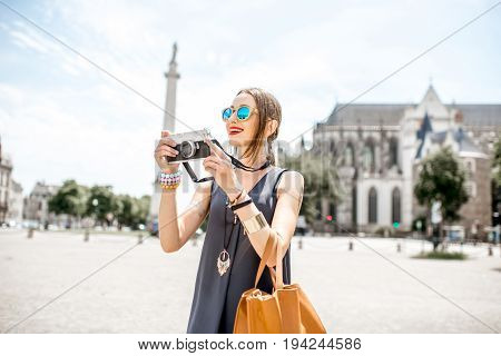 Young woman standing with photo camera on the square with Louis column and saint Pierre cathedral on the background in Nantes city in France