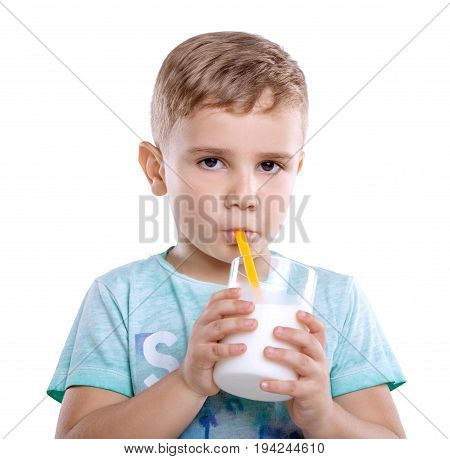 A beautiful little kid in a blue T-shirt with a glass of a tasty milk. Delightful little baby boy is drinking fresh milk from a bright yellow straw. Close-up portrait of amazing boy drinks a glass of milk isolated on white background.