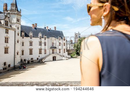 Woman enjoying the view on the Dukes castle in Nantes city in France. Image focused on the castle