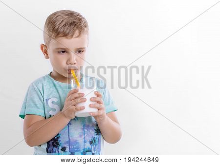 Pretty little boy in the blue t-shirt is drinking milk from a yellow straw on a gray background. Beautiful child with glass of milk on gray background. Healthy eating little boy is drinking milk from a yellow straw.