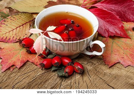a rosehip tea and colored autumn leaves