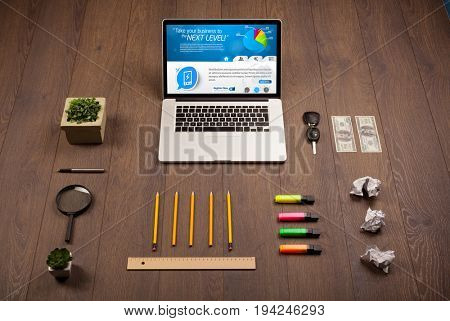 Laptop on office wooden desk with business website on screen