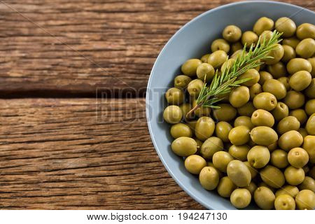 Garnished marinated olives in bowl on wooden table