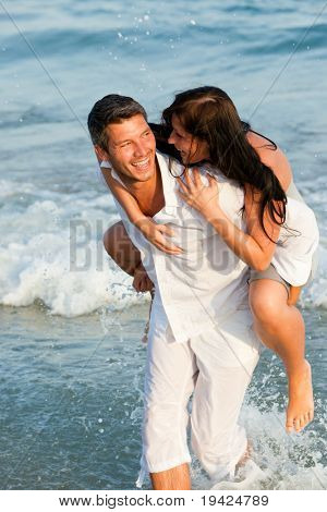 Playful Happy positive expressing couple of men and women smiling walking down the coast beach