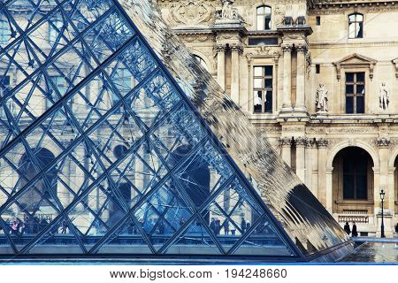 Paris, France -  2 March 2015: The modern Louvre glass pyramid against the historic Renaissance palace facade.