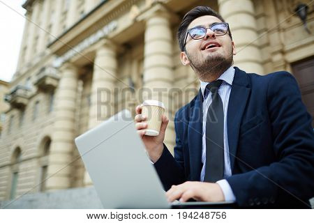 Modern broker with hot drink and laptop working in urban environment