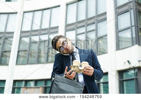 Busy broker with two glasses of coffee and briefcase calling in the city