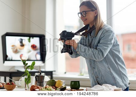 Self-employed food-photographer shooting served table in studio
