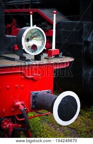 Warsaw Poland a museum of old retro steam locomotives. In the frame a flashlight and a buffer. Color red black white green